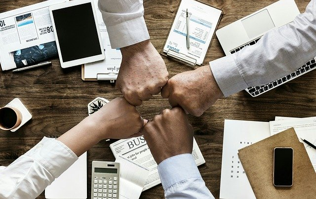 Team Handschlag auf Geschäftsschreibtisch